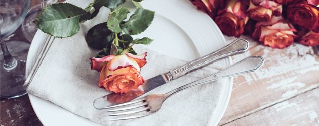 Restaurant table with cutlery, linen napkin and a rose